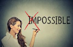 happy woman converting the word impossible to possible - stock photo