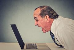furious business man working on computer, screaming - stock photo