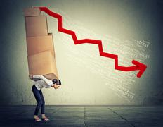 Stressed woman carrying pile of large boxes - stock photo