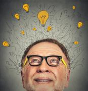 Stock Photo of Thinking elderly man with question signs and light idea bulb above head