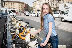 Beautiful woman taking rent bicycle in the city Stock Photos