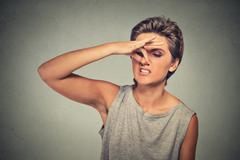 headshot woman pinches nose with fingers hand looks with disgust away somethi - stock photo