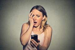 Anxious scared young girl looking at phone seeing bad news Stock Photos