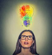 woman with glasses has brilliant colorful idea looking up at light bulb - stock photo