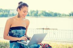 Amused young woman working with her notebook laptop sitting on a lawn - stock photo