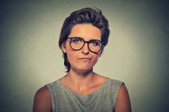 Skeptic. Doubtful woman in glasses looking at you Stock Photos
