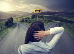 business woman in front of two roads thinking deciding - stock photo