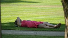 Woman lying on grass on a sunny day in Warsaw Stock Footage
