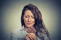 Sad young woman tired of diet restrictions craving sweets chocolate Stock Photos