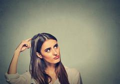 Contused thinking woman bewildered scratching her head seeks a solution - stock photo