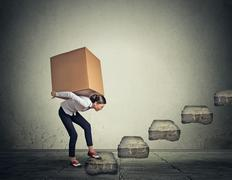 Difficult task concept. Young woman carrying heavy box upstairs - stock photo