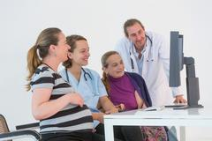 Two doctors, pregnant patient and her mother - stock photo