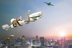 Younger man flying mid air with belonging luggage and passenger plane over be Stock Photos