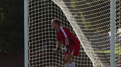 A goalie dives to block a soccer ball and misses Stock Footage