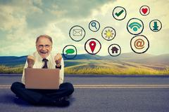 Happy elderly man working on computer using social media application - stock photo