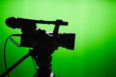 Silhouette of digital video camera in front of the green screen Stock Photos