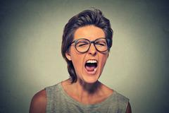 Angry young woman with glasses screaming Stock Photos