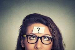 Thinking woman with question mark on gray wall background Stock Photos
