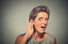 surprised young nosy woman hand to ear gesture secretly listening - stock photo