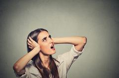 Annoyed stressed woman covering her ears, looking up loud noise upstairs Stock Photos