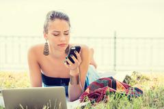 sad skeptical unhappy serious woman texting on phone outdoors in park - stock photo