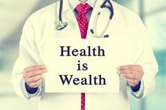 Doctor hands holding white card sign with health is wealth text message Kuvituskuvat
