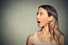 Woman talking with sound coming out of her open mouth Stock Photos