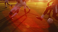 A soccer player tries to slide tackle his opponent at sunset - stock footage