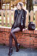 Happy beautiful woman with long legs sitting in the park Stock Photos