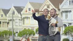 Asian Man Takes Photos With His Boyfriend And Dog, In Front Of Painted Ladies Stock Footage