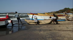 Men push a boat towards water Stock Footage