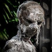 Mummified corpse wrapped in a bandage worn down. - stock photo