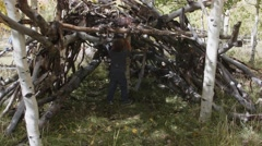 A boy playing in a hut built from sticks Stock Footage