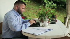 Tired man in front of laptop on porch Stock Footage