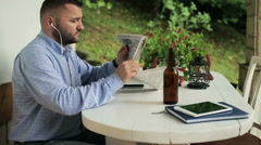 Man read newspaper and listen to music on smartphone - stock footage