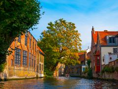 Medieval houses along canals of Bruges in autumn time - stock photo