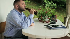 Happy man drinking beer by the table on house porch Stock Footage