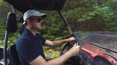 A wide shot of a person steering side by side vehicle in thick green forest Stock Footage