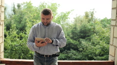 Young, handsome man with tablet computer standing on terrace Stock Footage