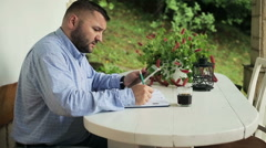 Young man with tablet computer writing notes in calendar - stock footage