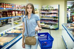 Beautiful young woman shopping for diary products at a grocery store/supermar Kuvituskuvat