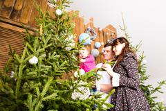 Family decorate the Christmas tree Stock Photos