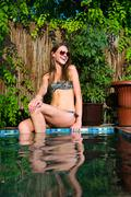 Beautiful happy woman in bikini sitting near swimming pool Stock Photos