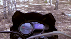 A shot of the handlebars, gages and gas tank of a speeding motorcycle as seen - stock footage
