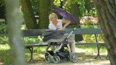 Stock Video Footage of Mother with baby stroller sitting on a bench in a park, Warsaw