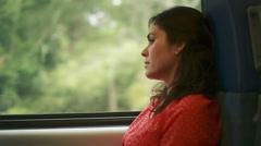 Beautiful woman looking pensive inside a train - stock footage