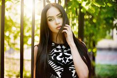 beautiful brunette woman outdoors portrait on a sunny day - stock photo