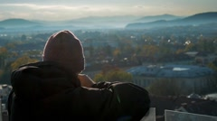 A yung man is looking over the city blocks as he is exploring it Stock Footage