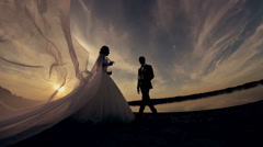 The groom kisses the bride at sunset on the beach silhouette Stock Footage