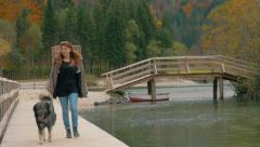 Stock Video Footage of Red haird girl is walking over bridge by beautiful lake